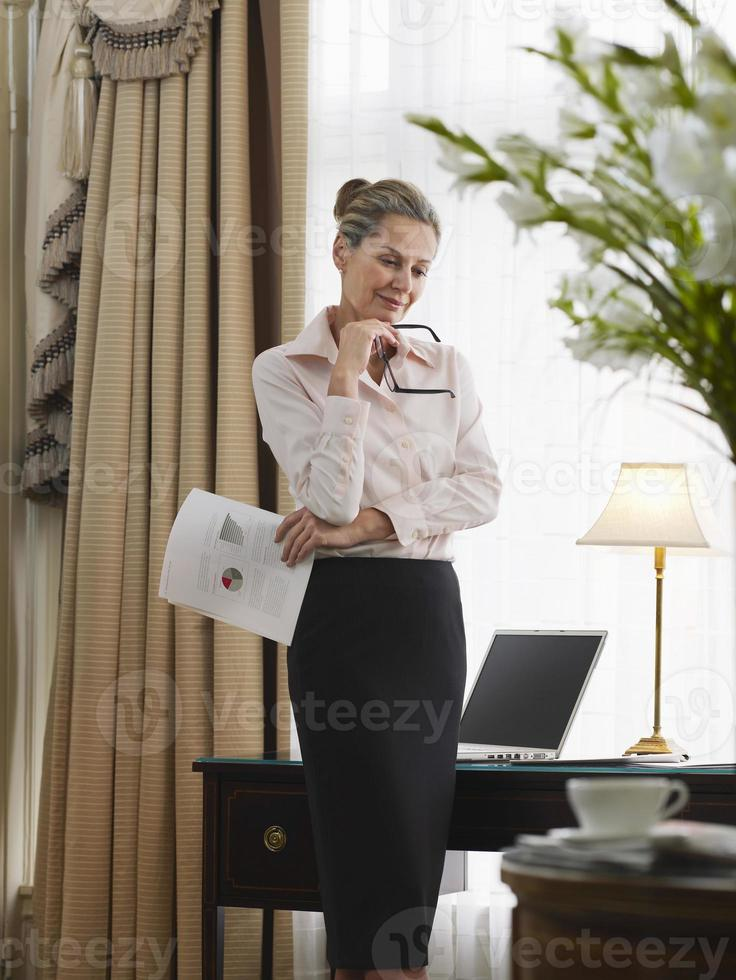 Empresaria reflexiva con documento en la oficina en casa foto