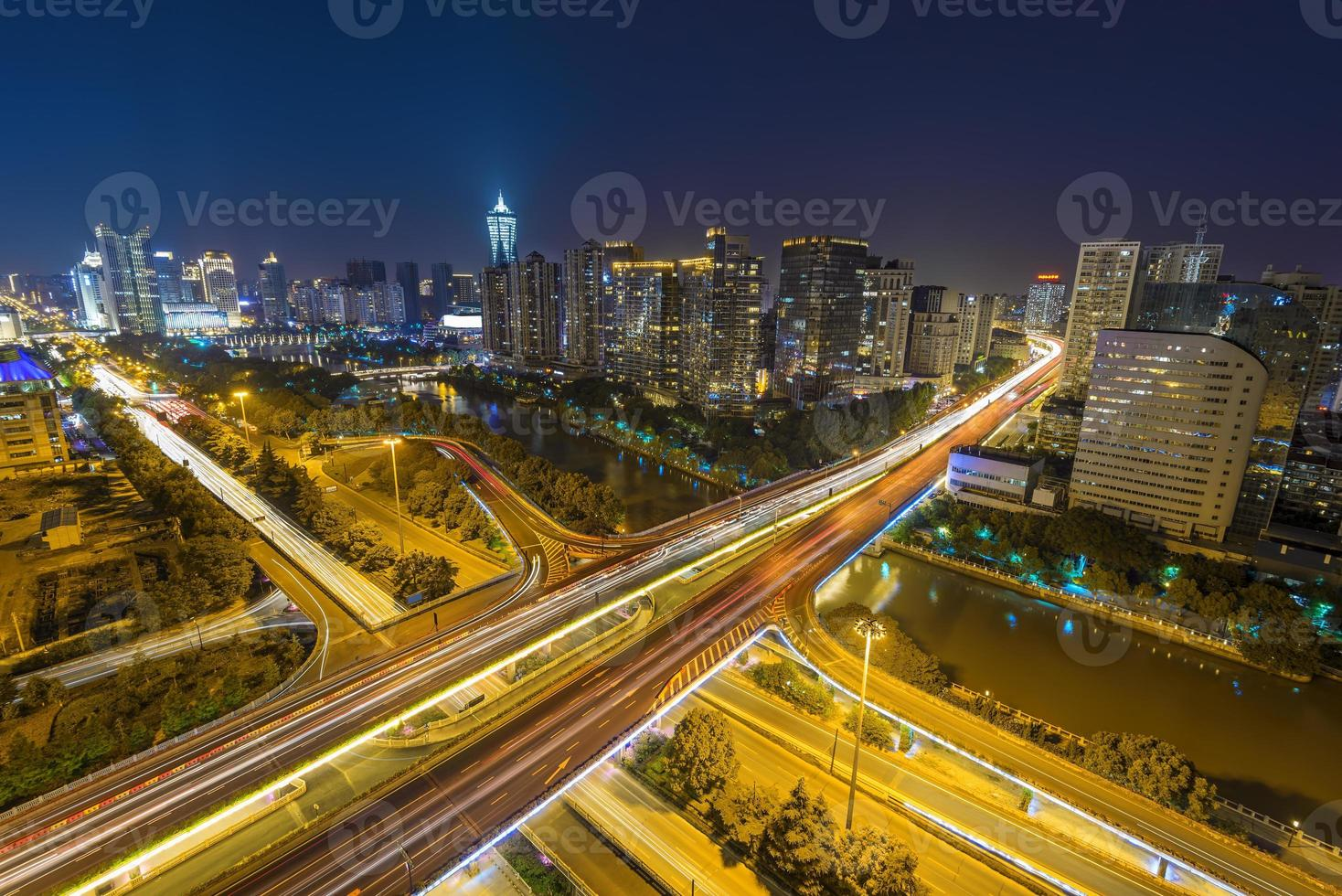 traffic light trails on overpass and cityscape at night photo