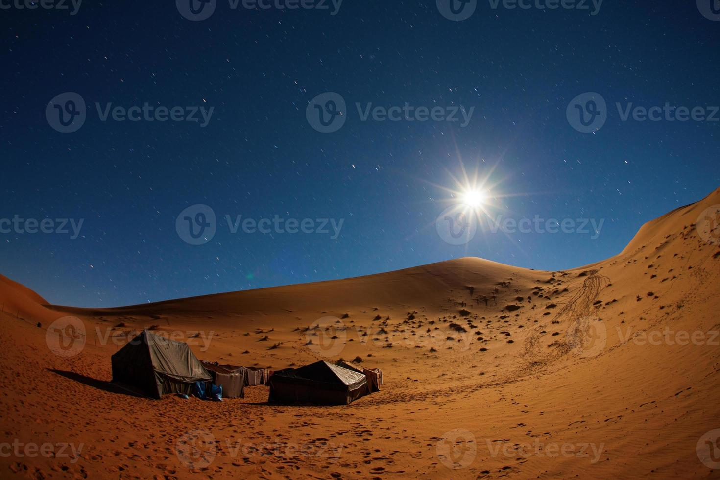 Camp in Sahara Desert night with moon and moving star photo