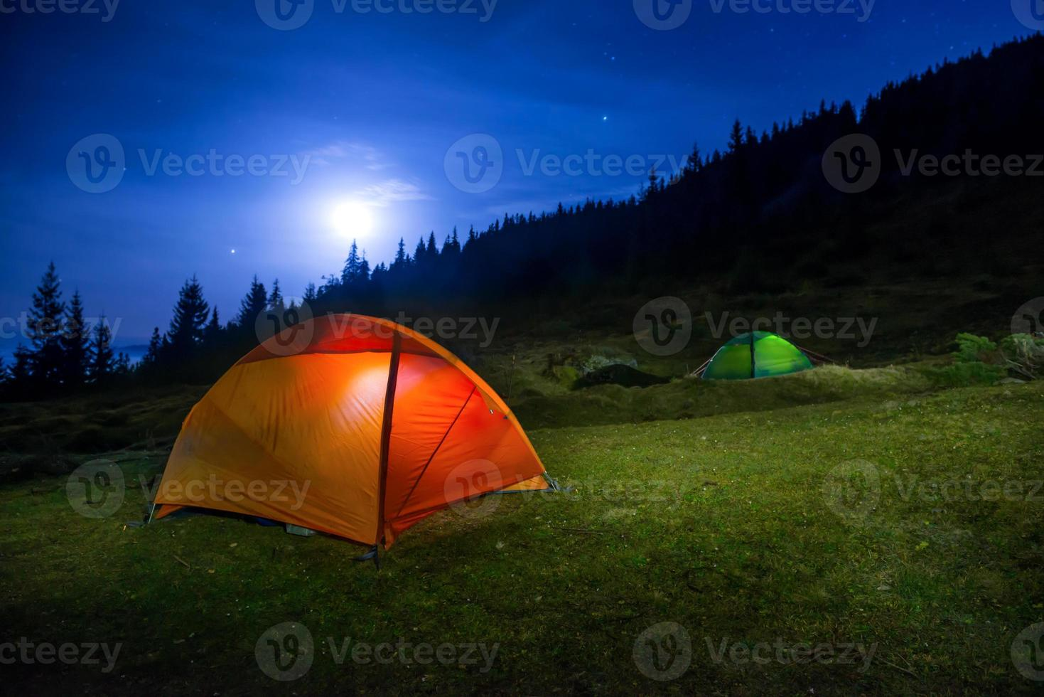 Two Illuminated orange and green camping tents photo