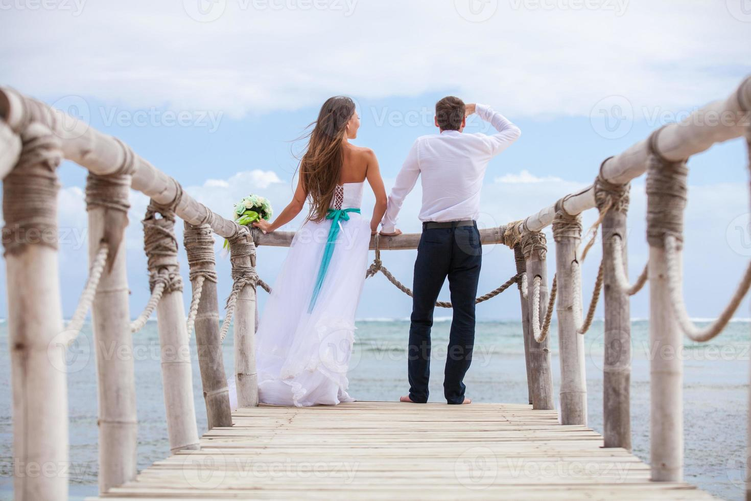 Bride and groom together on a wharf photo