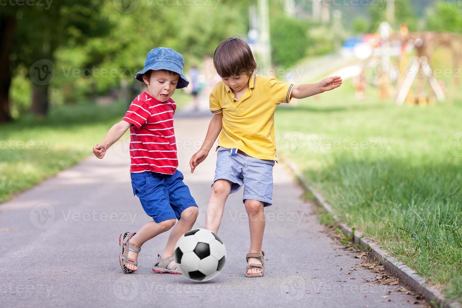 dos lindos niños pequeños, jugando al fútbol juntos, en verano foto