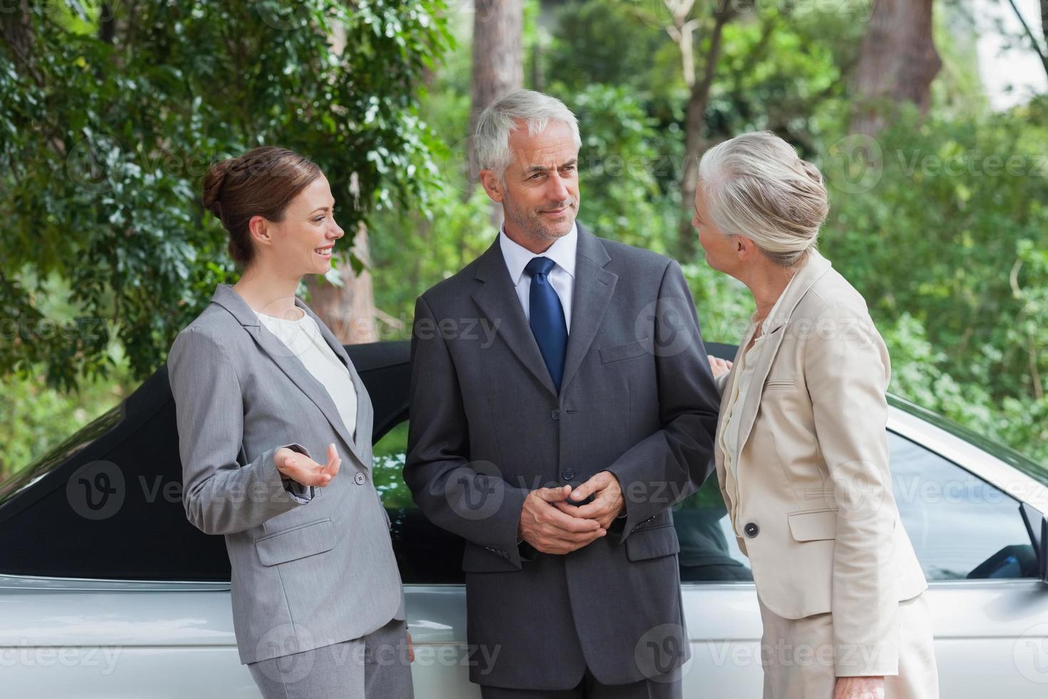 empresarios sonrientes hablando juntos por elegante cabriolet foto
