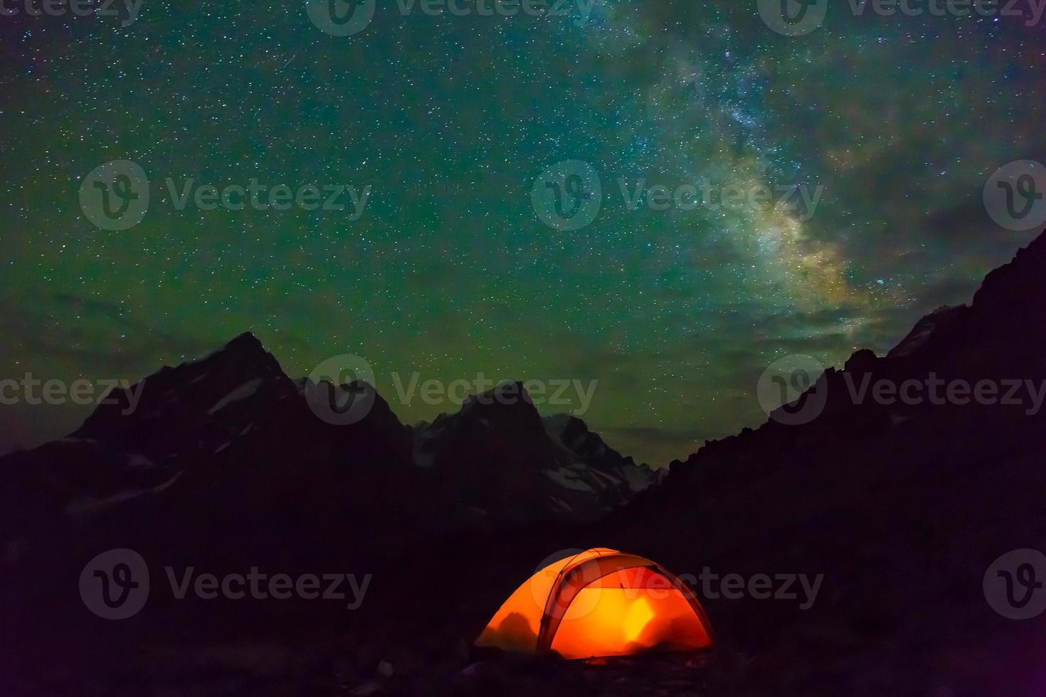 Night mountain landscape with illuminated tent photo