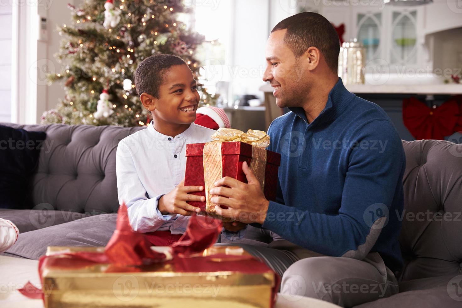 padre e hijo abriendo regalos de navidad en casa juntos foto
