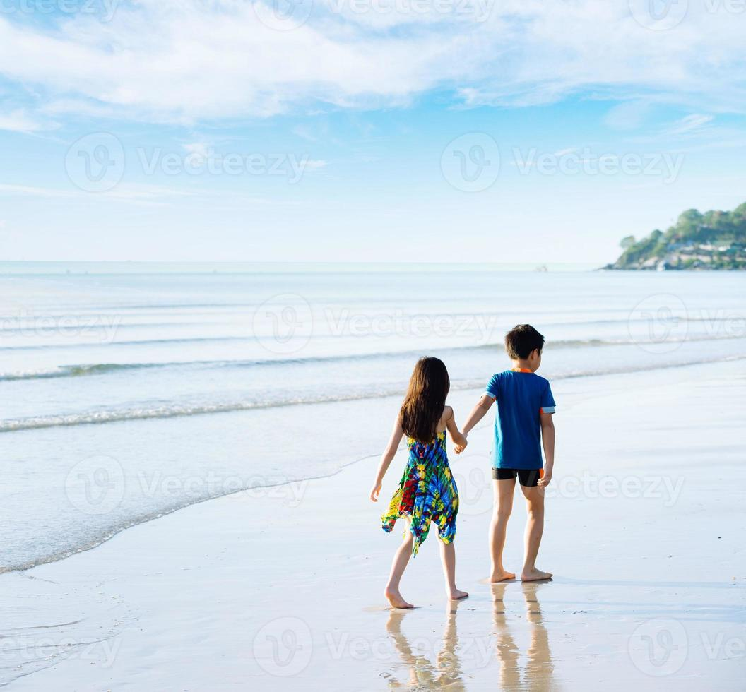 Brother sister holding hand walk on the beach photo
