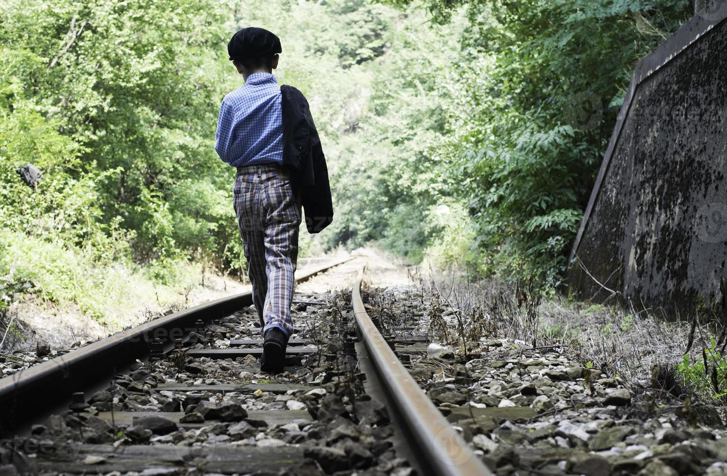 niño caminando en ferrocarril foto