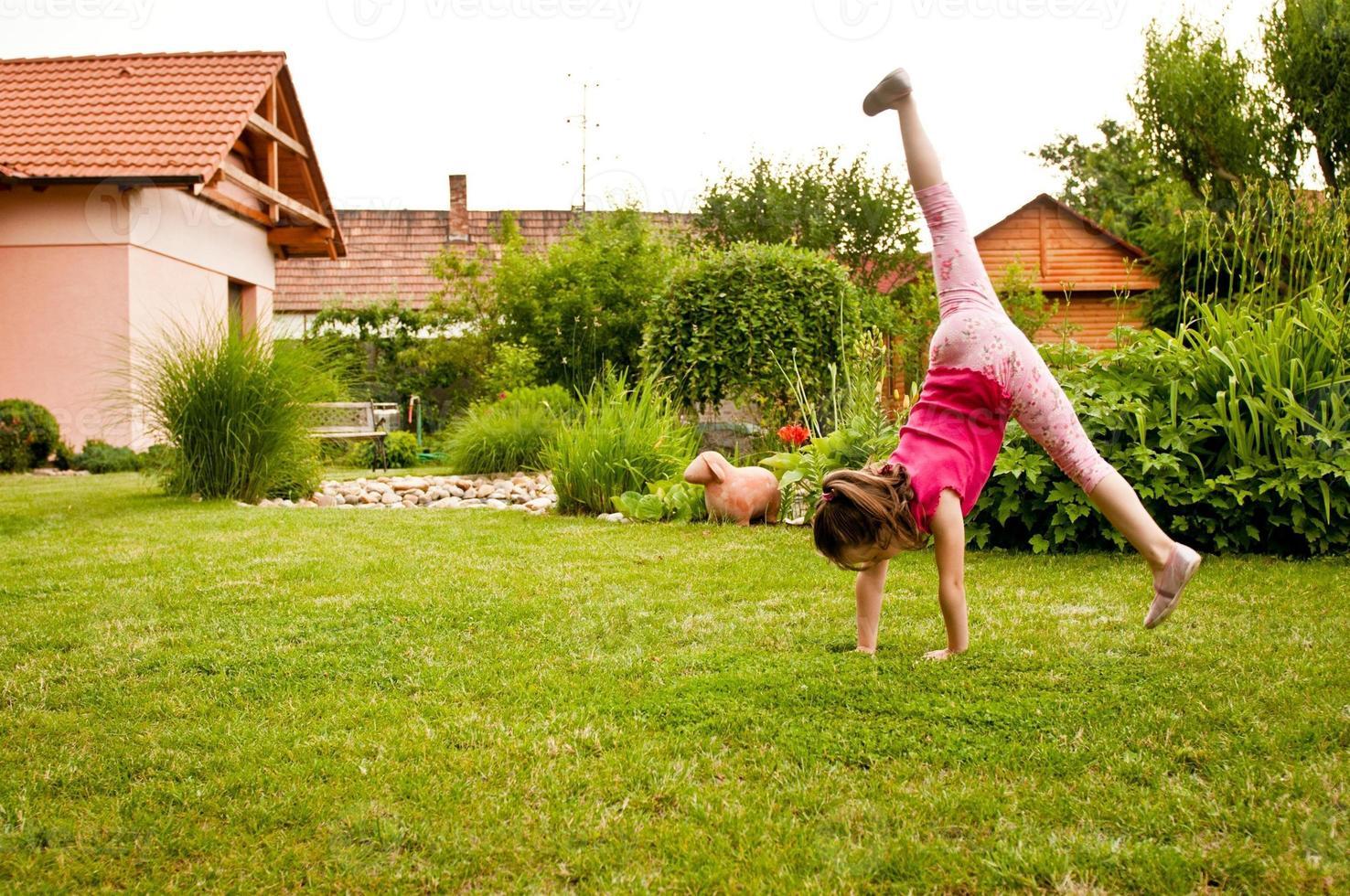 Child doing cartwheel in backyard photo