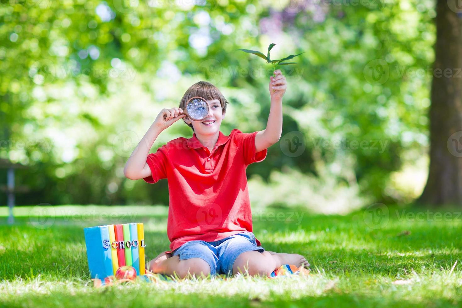 Happy child with magnifying glass photo