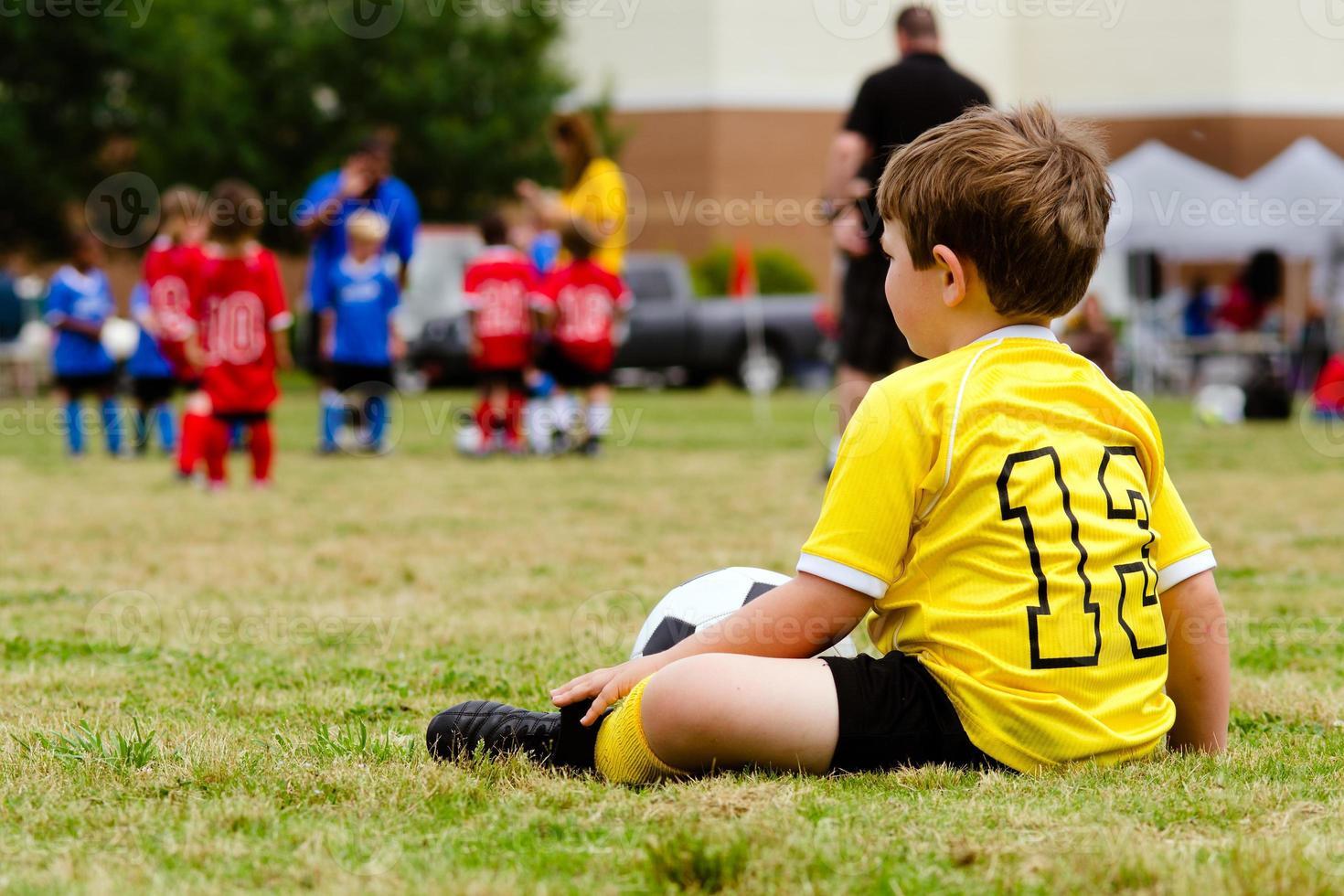 niño en uniforme viendo fútbol juvenil organizado foto