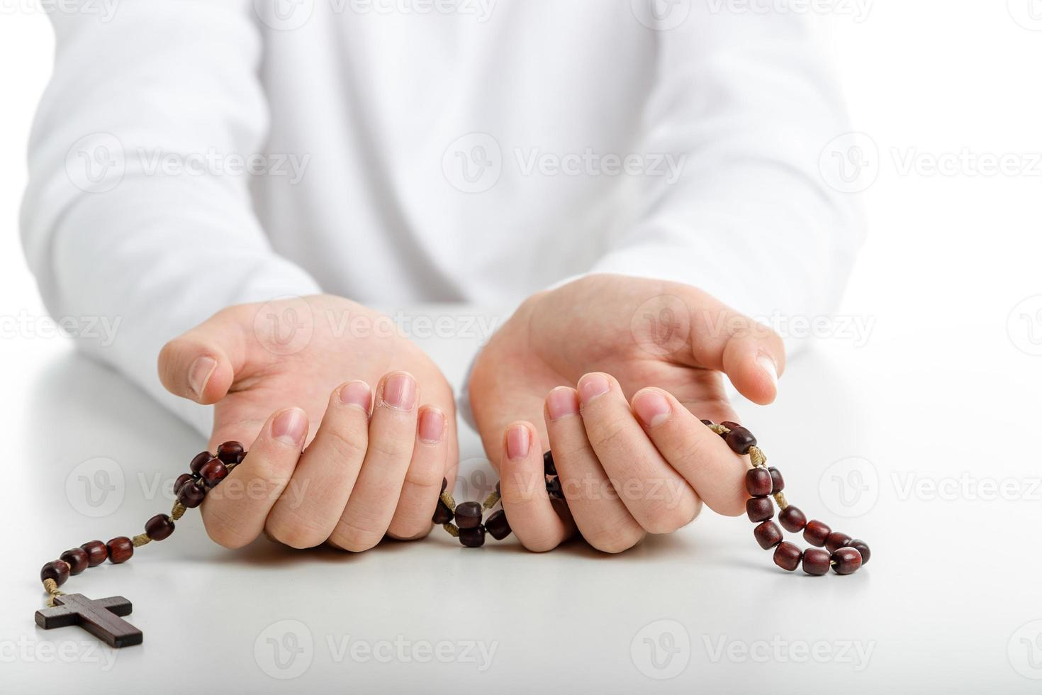 Child hands offer wooden rosary beads photo