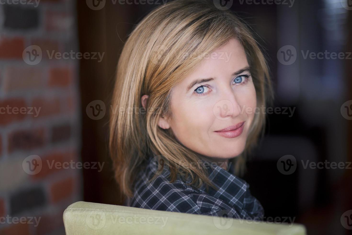 mujer madura rubia sonriendo mientras mira a la cámara foto