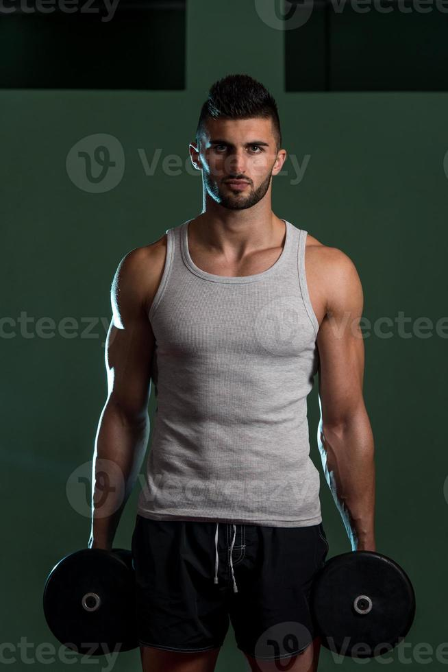 Men In Gym Exercising With Dumbbells photo