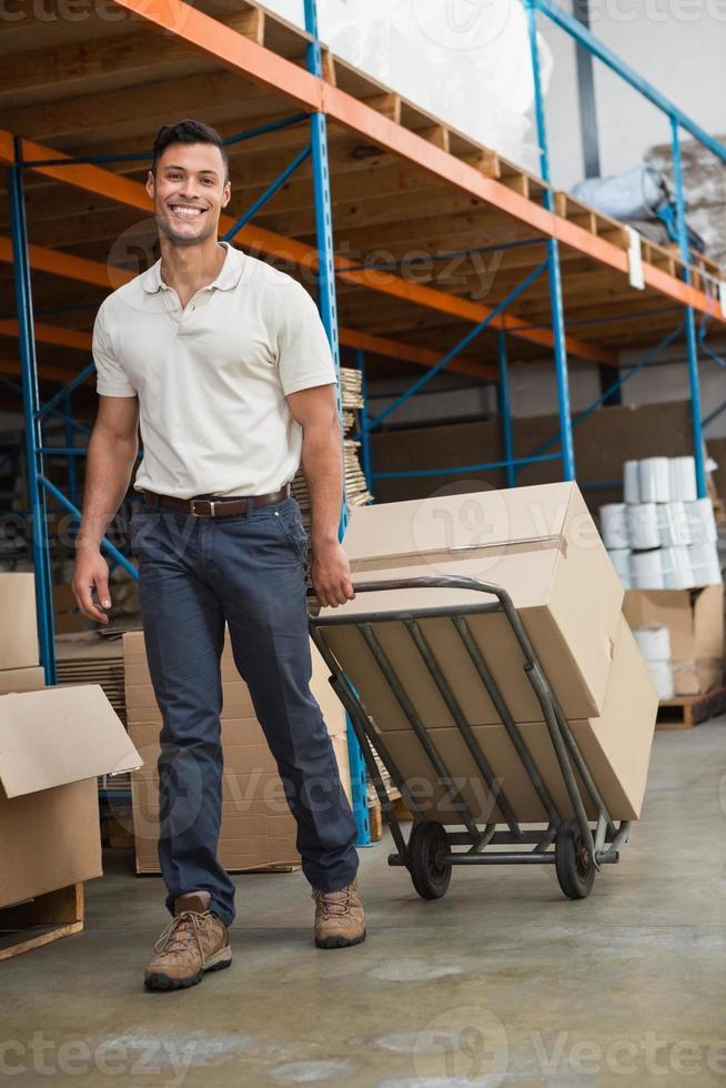 trabajador de almacén moviendo cajas en carro foto