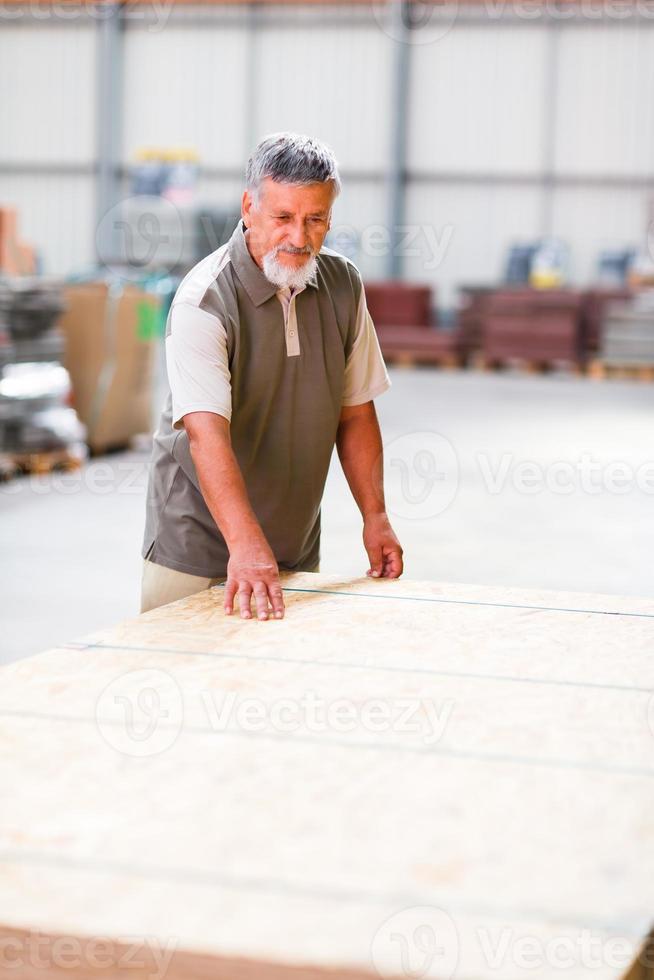 Senior hombre comprando madera de construcción en una tienda de bricolaje foto