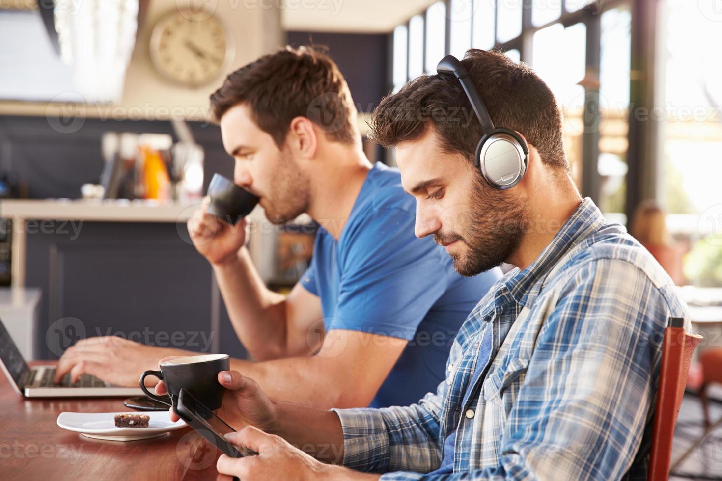 Dos hombres jóvenes que trabajan en computadoras en una cafetería foto