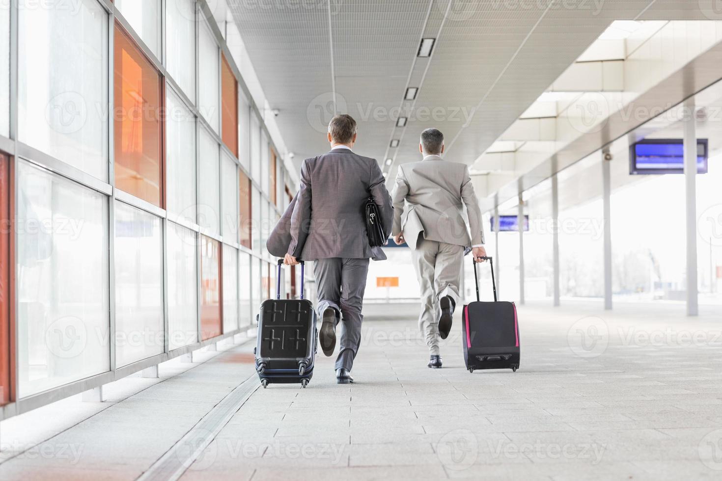 Businessmen with luggage running on railroad platform photo