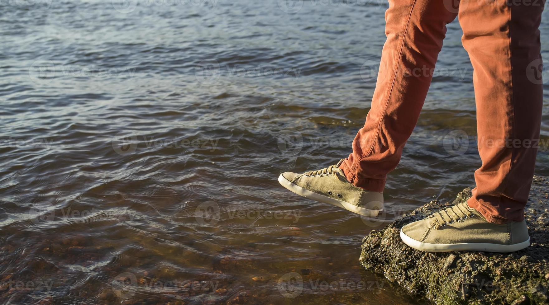 close-up van de benen van de man die stap in de rivier neemt foto