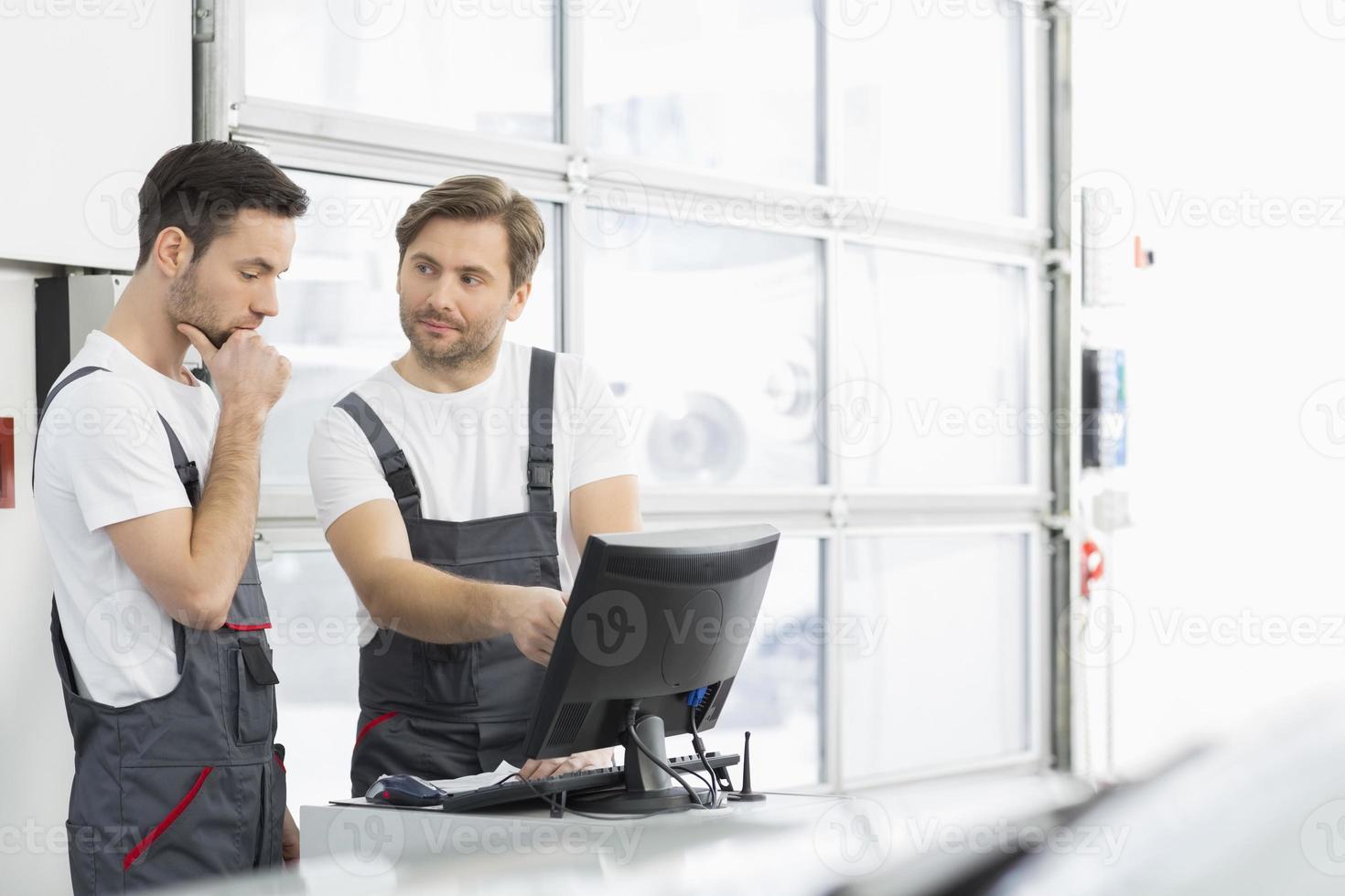 Mécanicien automobile masculin conversant en atelier de réparation photo