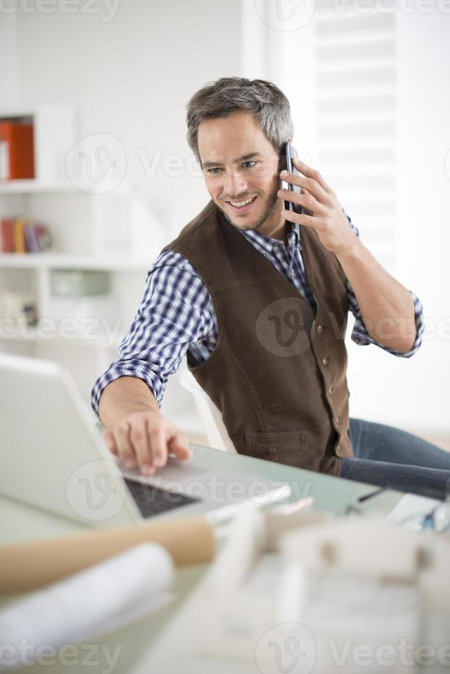 een architect die op zijn laptop werkt terwijl hij aan de telefoon is foto