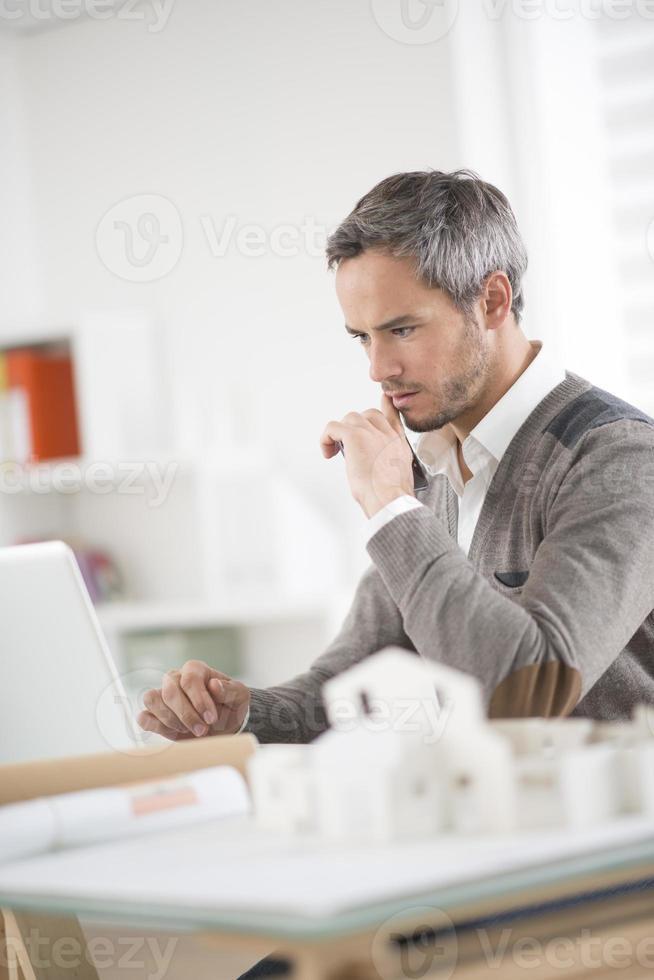 architect werkt op zijn laptop op kantoor foto