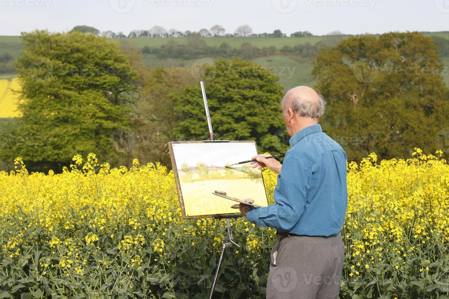 A senior male artist painting a beautiful landscape photo