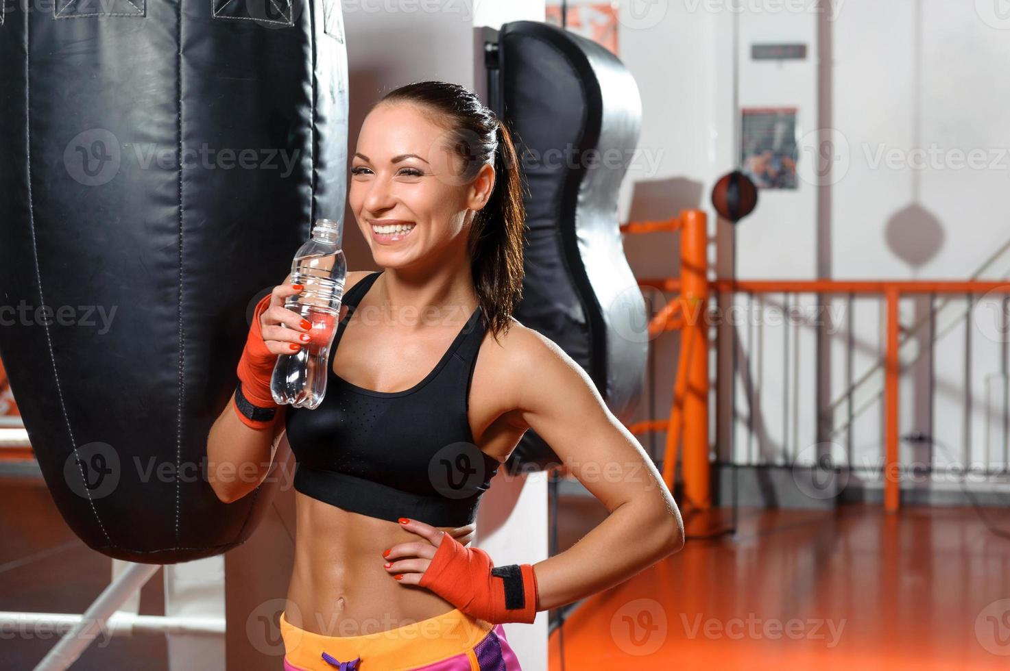 Female kickboxer drinks water photo