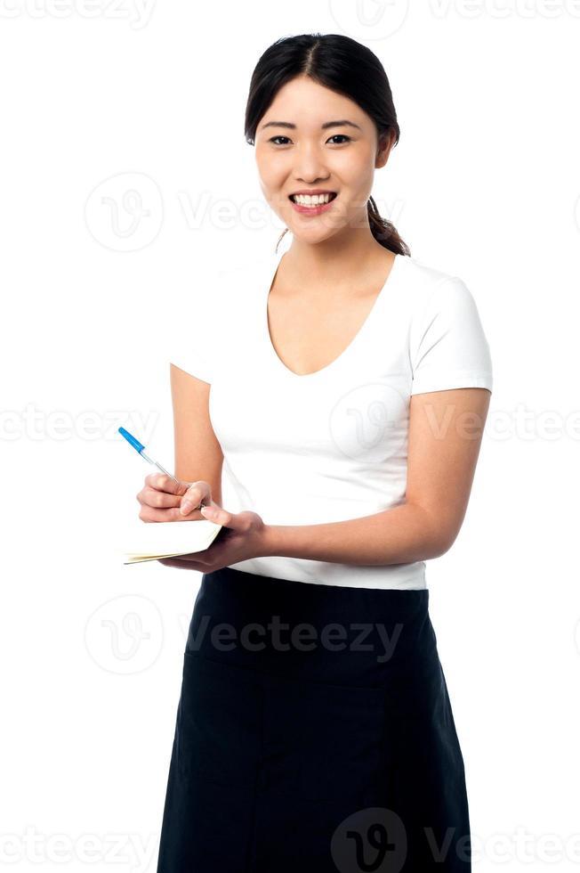 jovem assistente feminina, anotando foto
