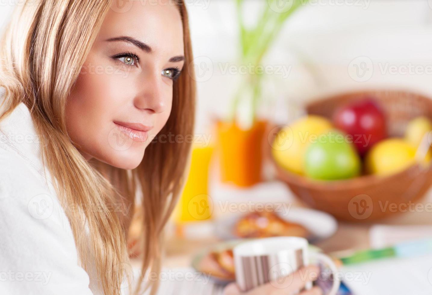 fêmea bonita tomando café da manhã foto