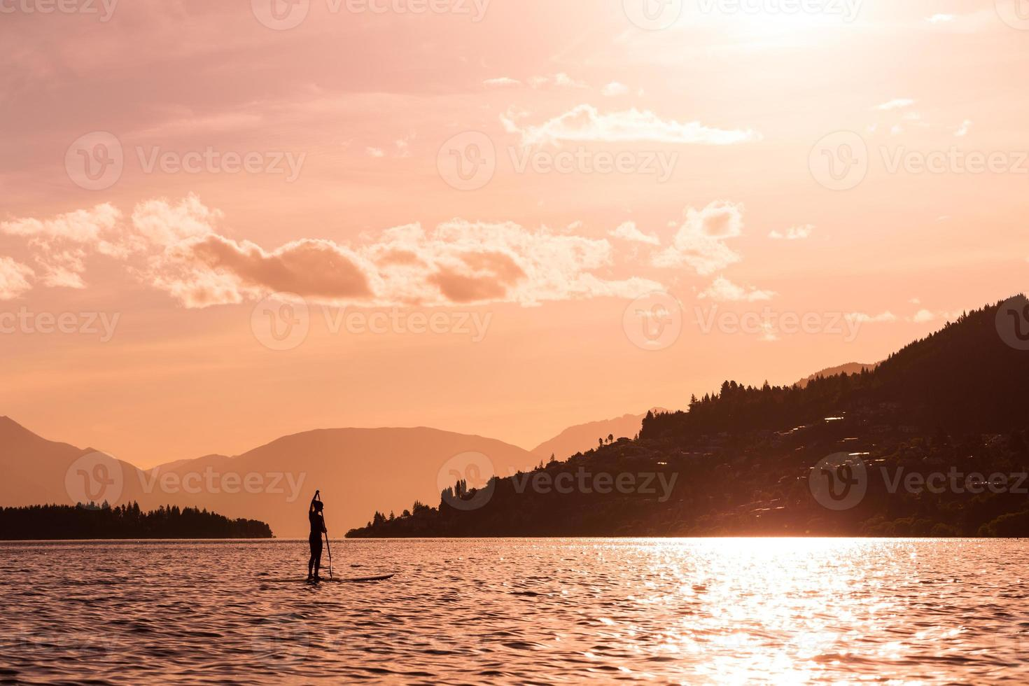 young female paddles a paddleboard photo