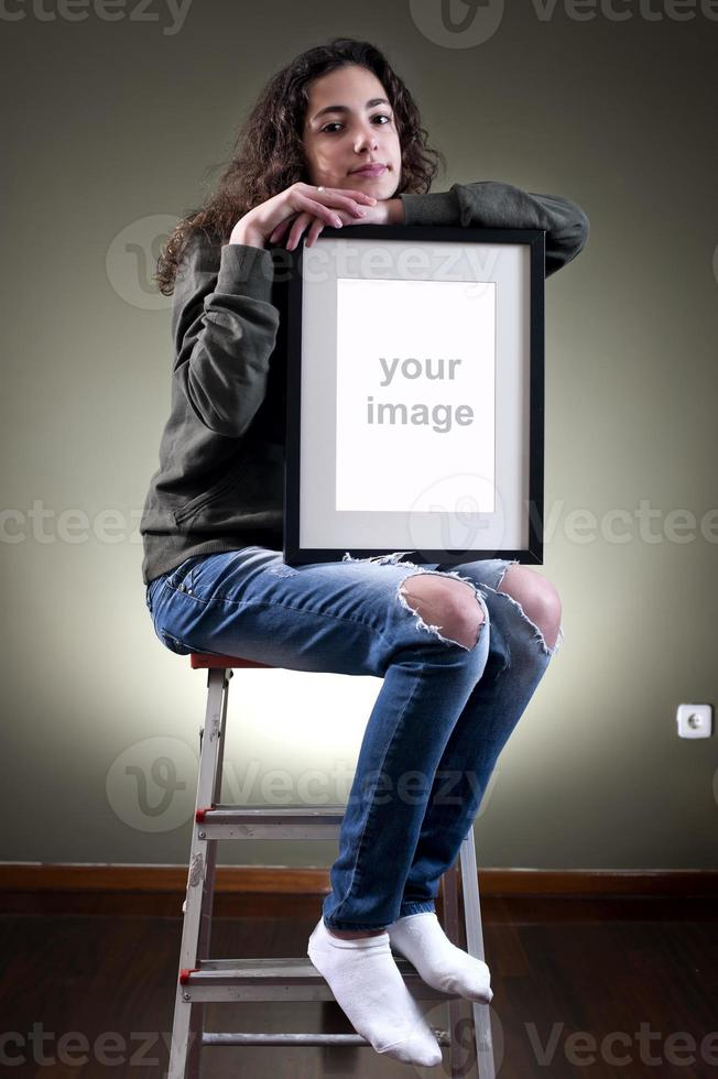 Young female holding picture frame photo