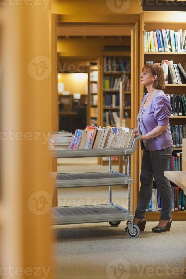 Serious female librarian pushing a cart photo