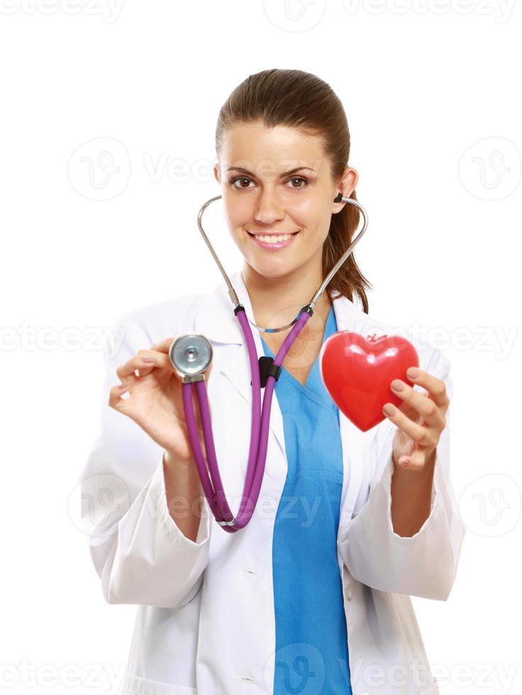 médica com estetoscópio segurando coração foto