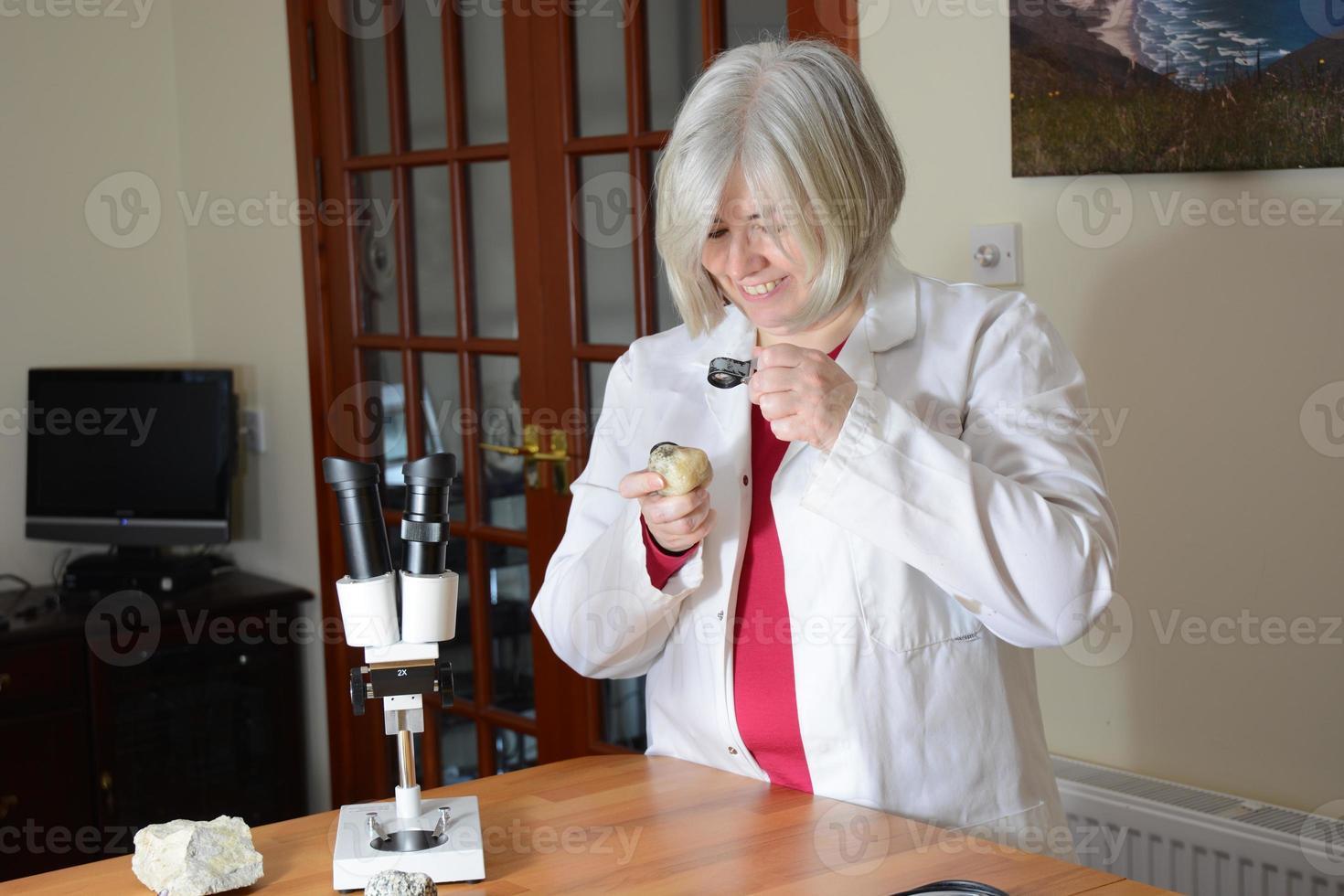 vrouwelijke wetenschapper die bij een rots glimlacht foto