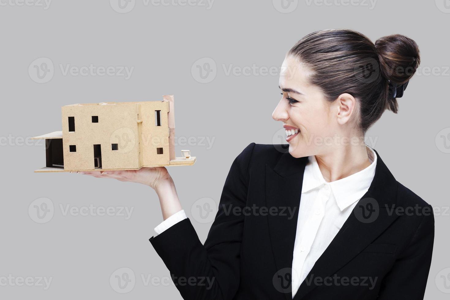 Female business agent holding house model photo
