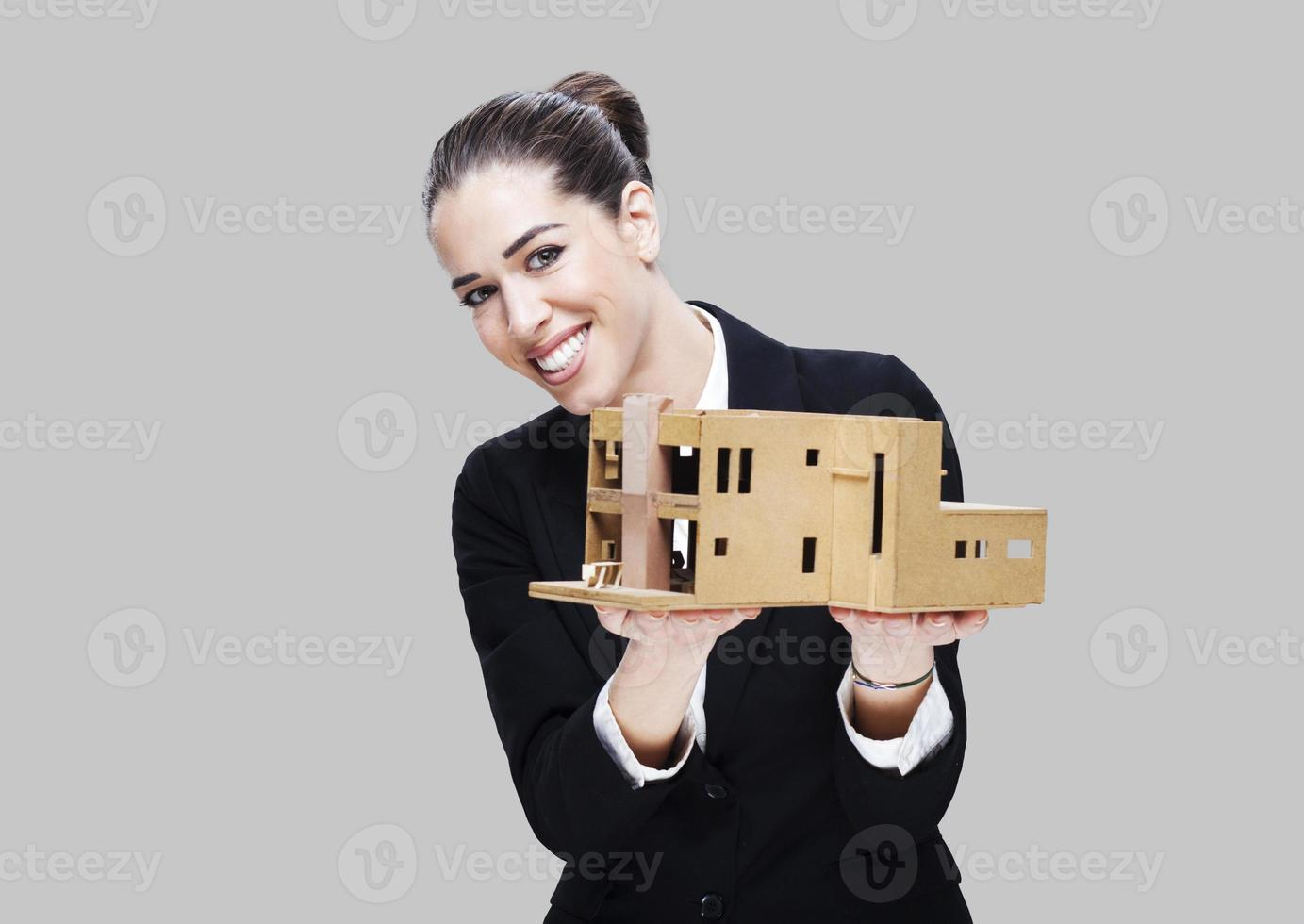 Female business agent holding house model photo