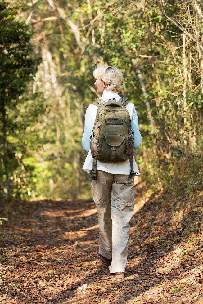 Senior mujer excursionista caminando en bosque foto