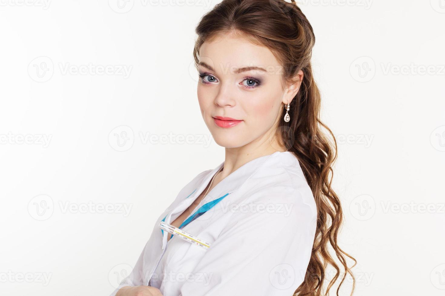Pretty young female doctor with thermometer photo