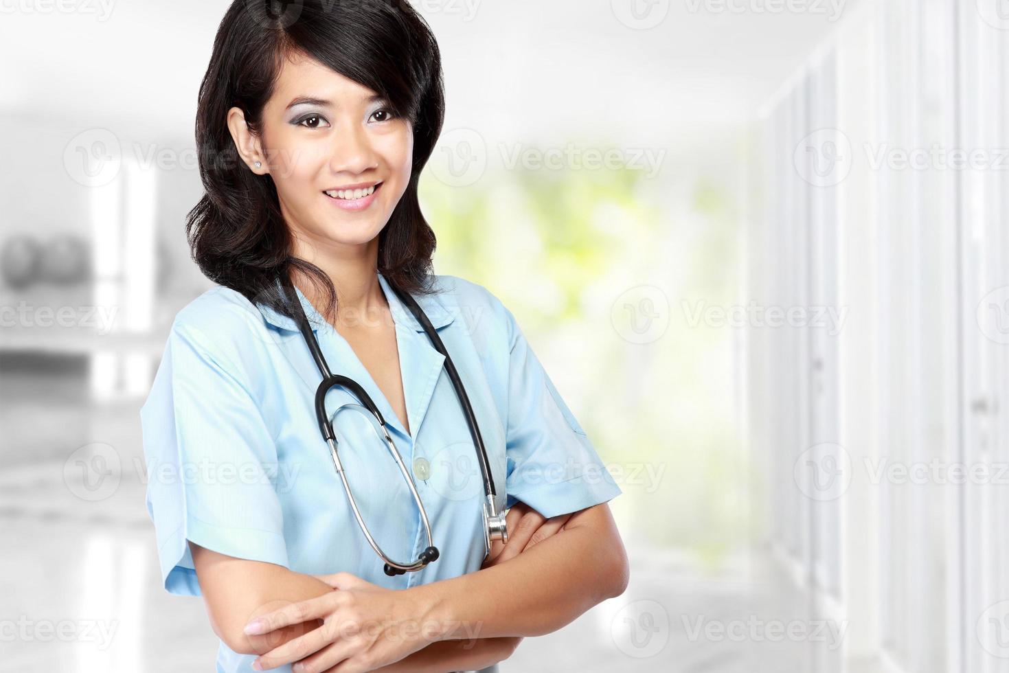 médico feminino de beleza com o braço cruzado foto