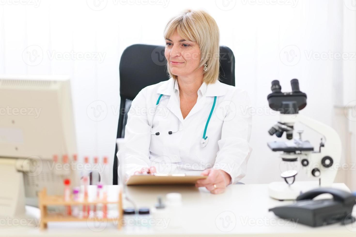 médica sênior trabalhando no escritório foto