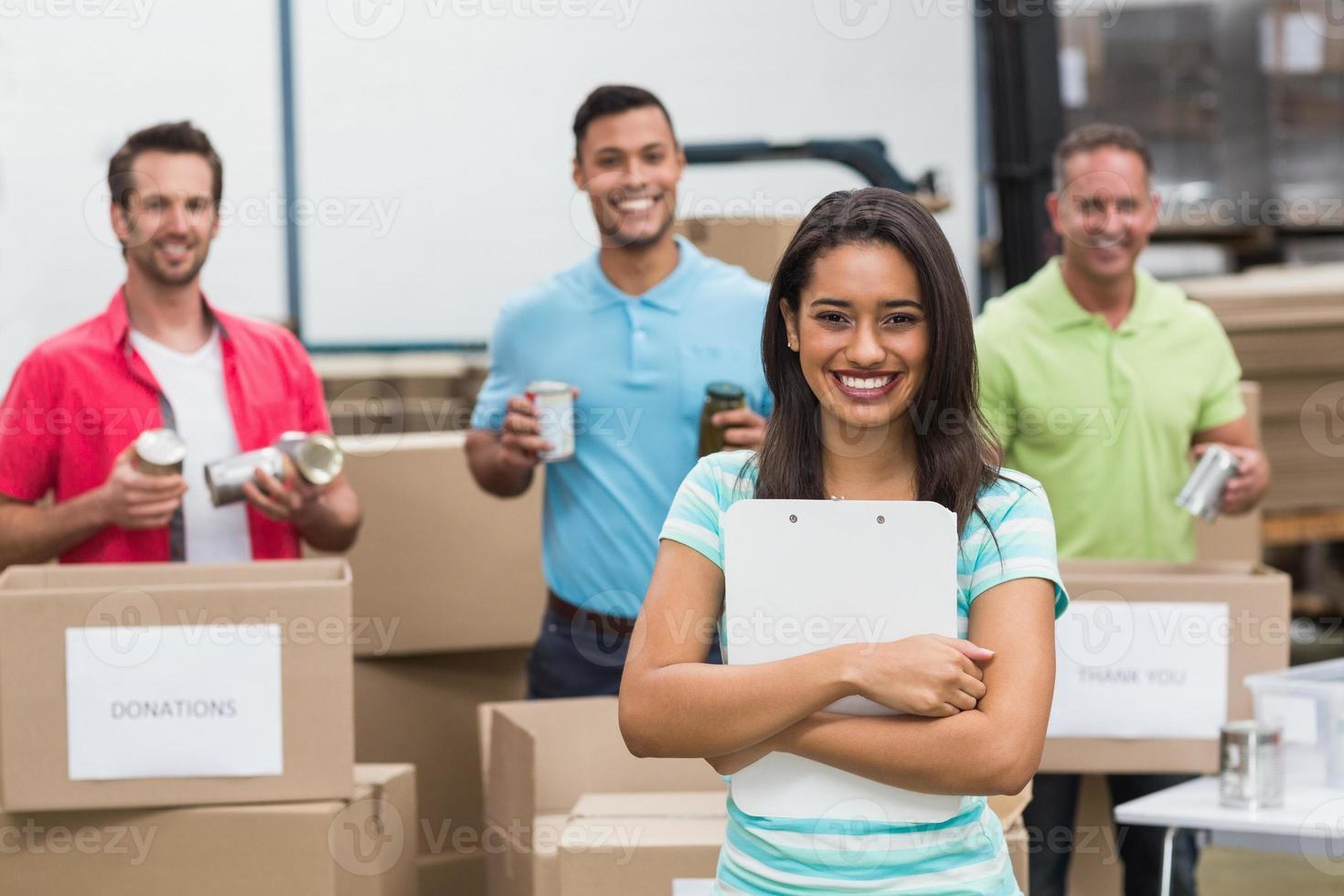 sonriente joven voluntario femenino con portapapeles foto