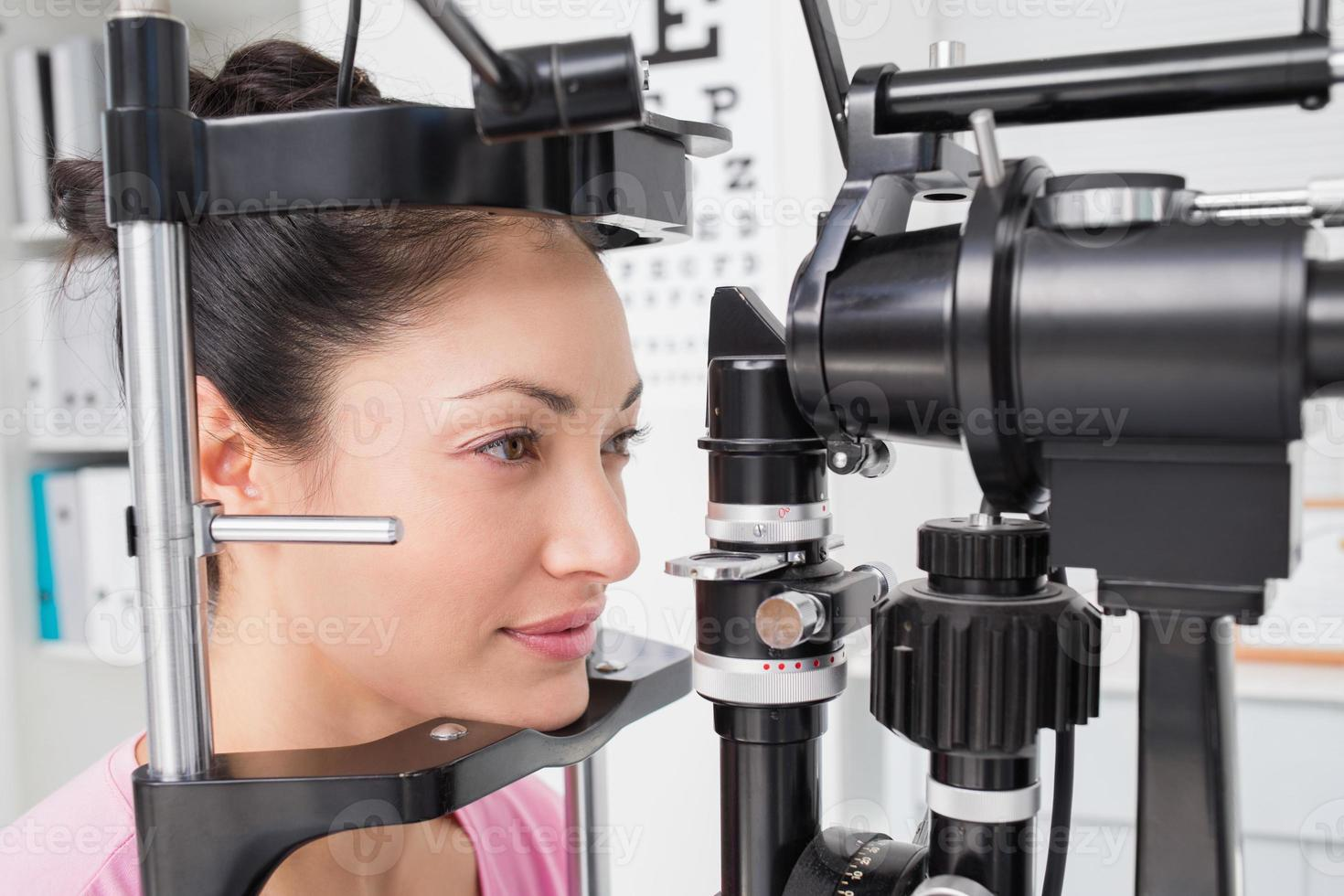 Female patient looking into slit lamp photo