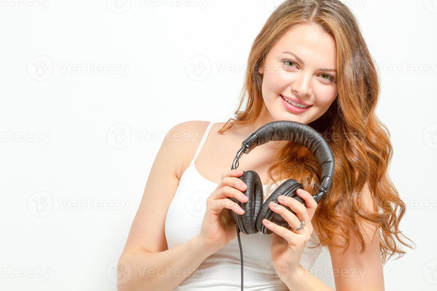 alegre mulher segura fones de ouvido no pescoço foto