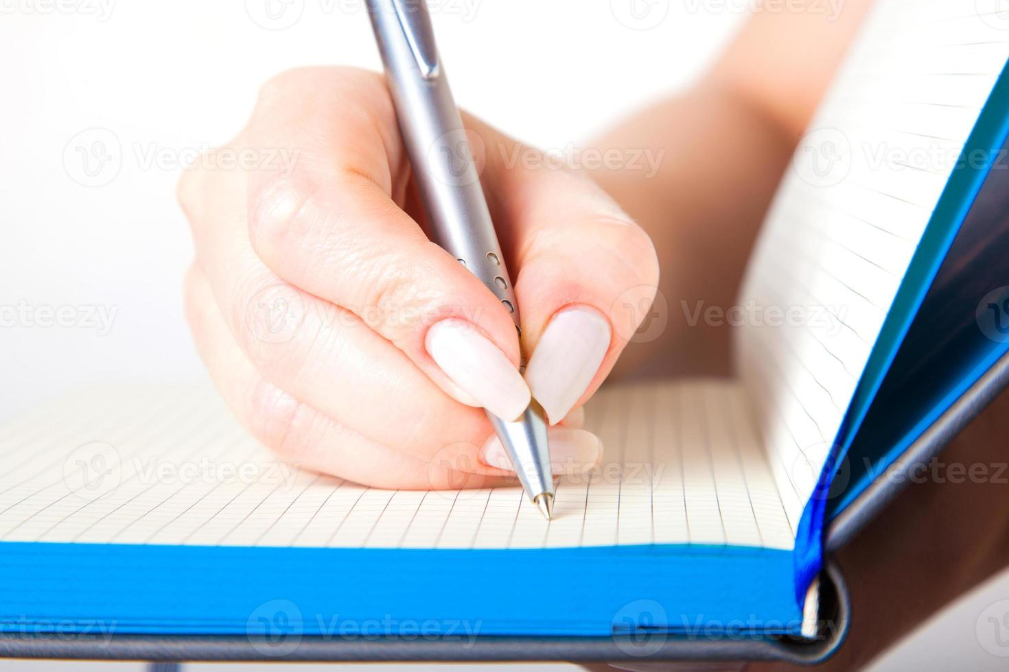 feminino mão escrevendo num caderno foto