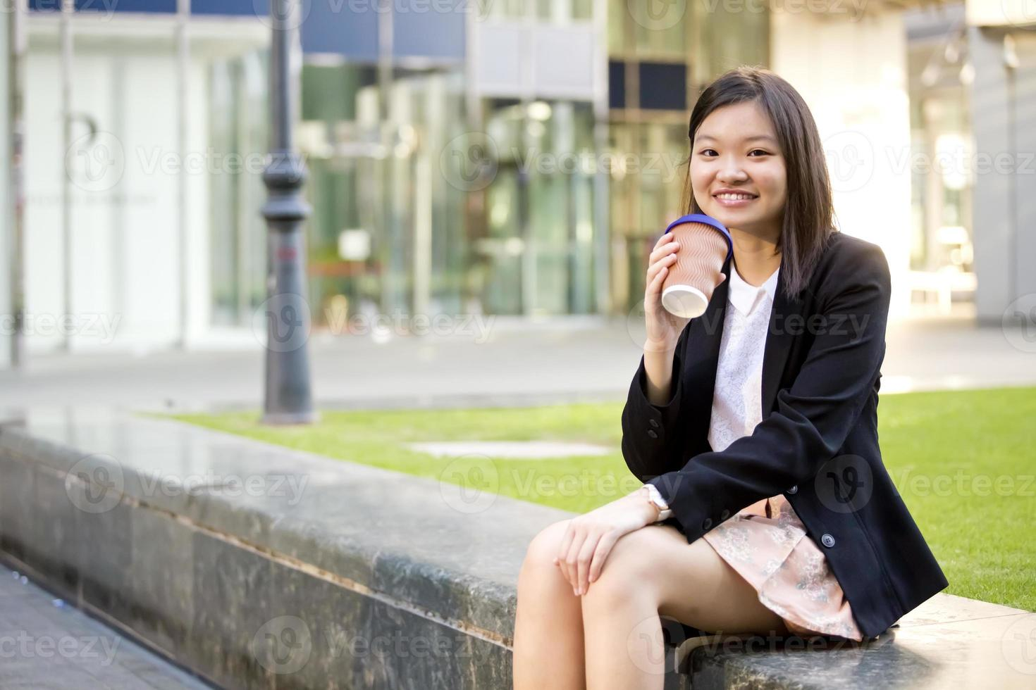Young female Asian executive holding file photo