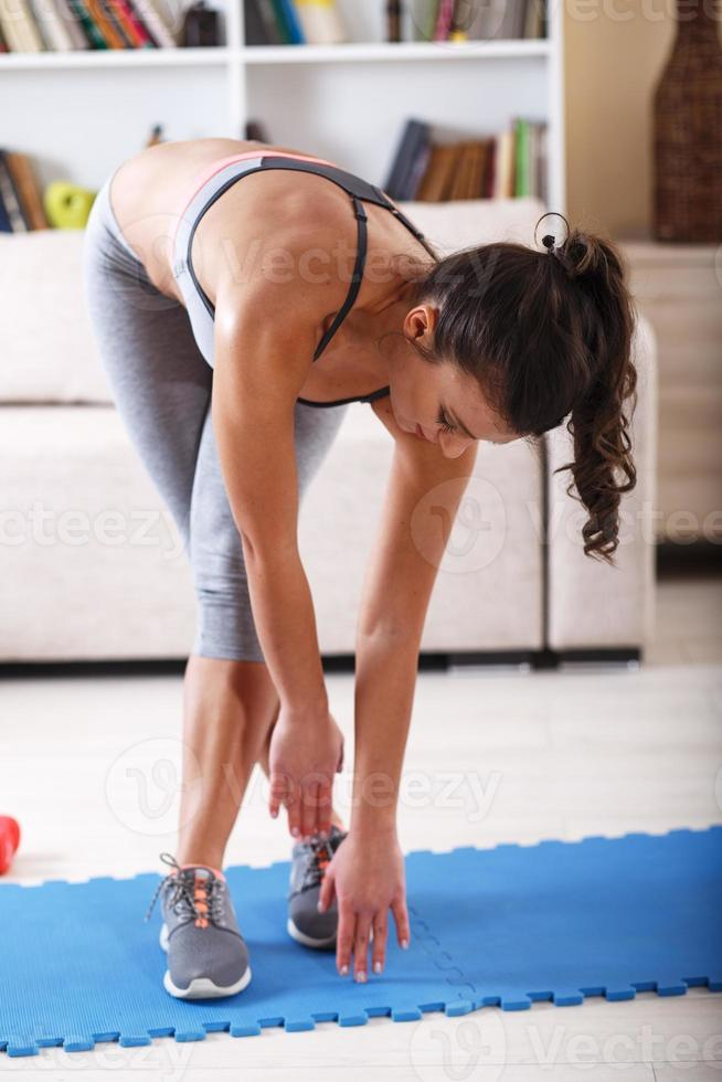Attractive female doing exercise at home. photo