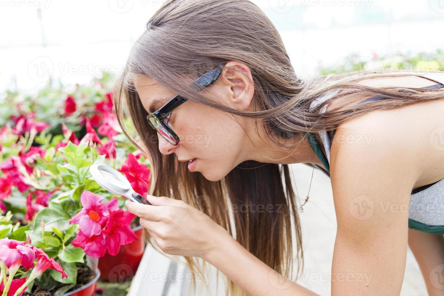 young female gardener monitors health of flowers photo