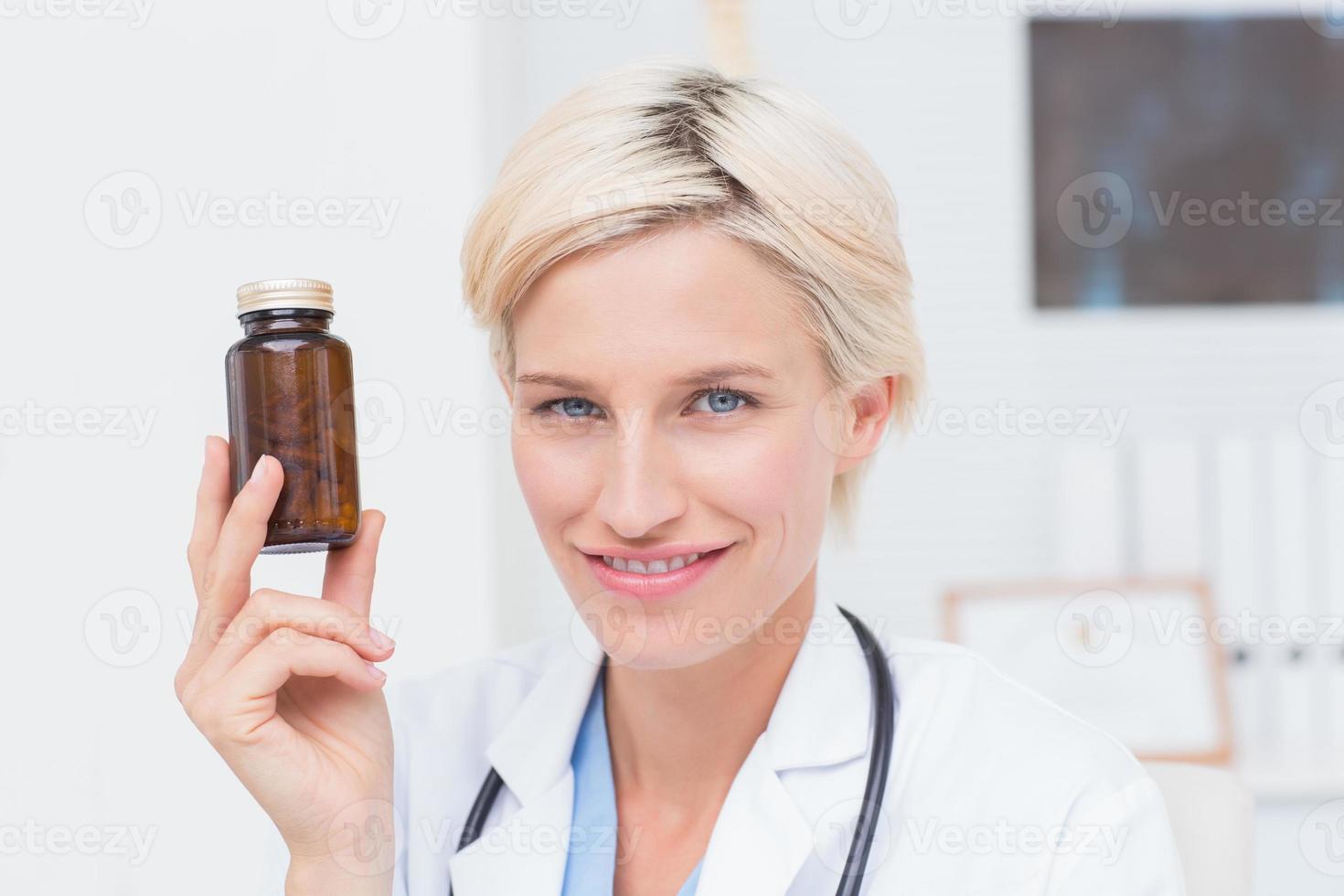 Confident female doctor holding medicine bottle photo