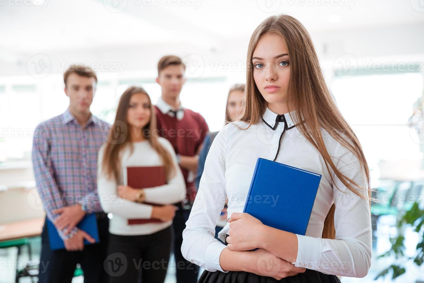 Female student standing with classmates on background photo