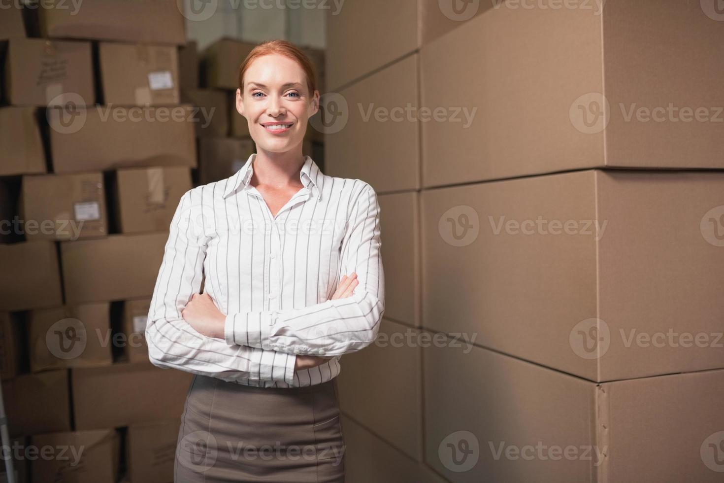 vrouwelijke manager met gekruiste armen in magazijn foto